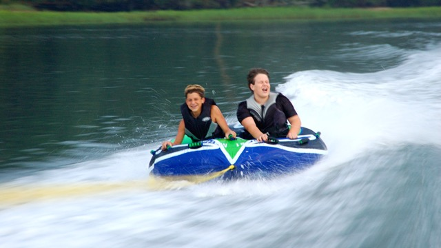 two kids tubing in hilton head on boat trip